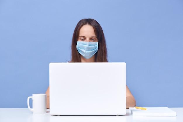 開いているラップトップとカップの近くの白い机に座って、オンライン学習に取り組んでいる愛らしい暗い髪の女性、白いtシャツと防護マスクを身に着けている女性。フリーランサー。