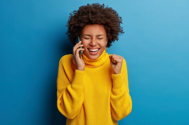 행복한 표정으로 휴대 전화를 사용하여 노란색 점퍼를 입은 사랑스러운 어두운 피부 성인 여성