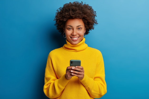 Adorable dark skinned adult woman dressed in yellow jumper using mobile phone with a happy expression