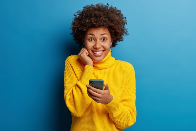 Adorabile donna adulta dalla pelle scura vestita in maglione giallo utilizzando il telefono cellulare con una felice espressione