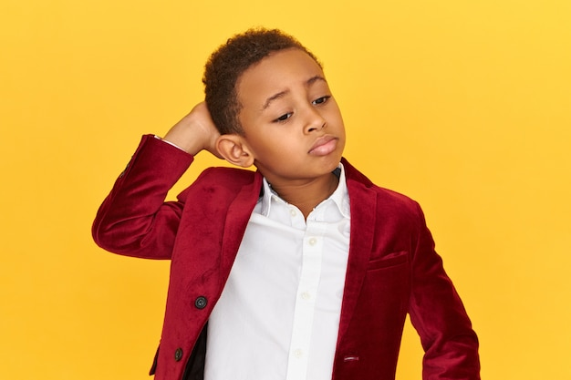 Adorable dark skinned little boy pouting lips and holding hand on back of his neck, having frustrated confused facial expression, posing isolated.