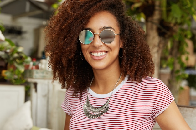 Adorable dark skinned smiling cute female with afro hairstyle wears fashionable sunglasses, enjoys summer recreation, sits against cafe interior, has pleasant talk with friend who sits opposite