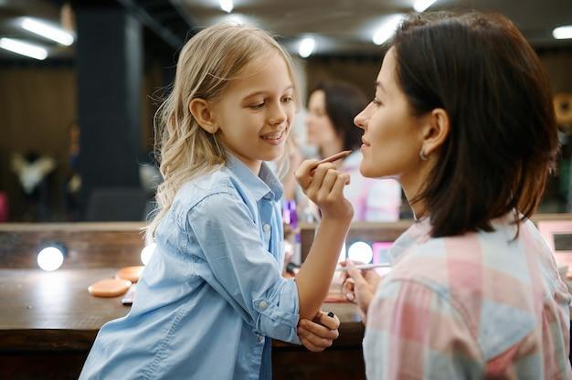 사랑스러운 딸이 살롱에서 그녀의 어머니에게 입술을 페인트