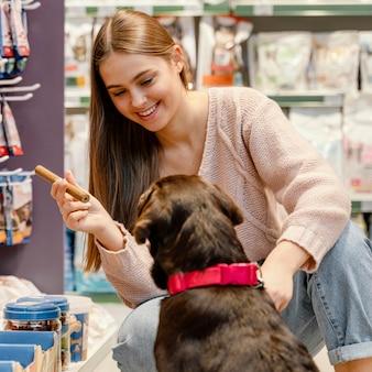 Очаровательная собака с владельцем женского пола в зоомагазине
