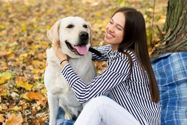 Прелестная собака с женщиной в парке