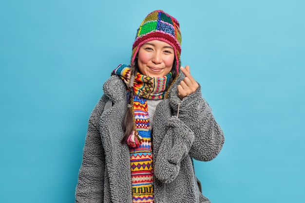 Adorable eastern asian girl dressed in winter clothing makes korean like sign shows mini heart expresses love going to have walk poses against blue studio wall