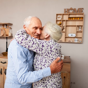 Adorable elderly couple hugging each other