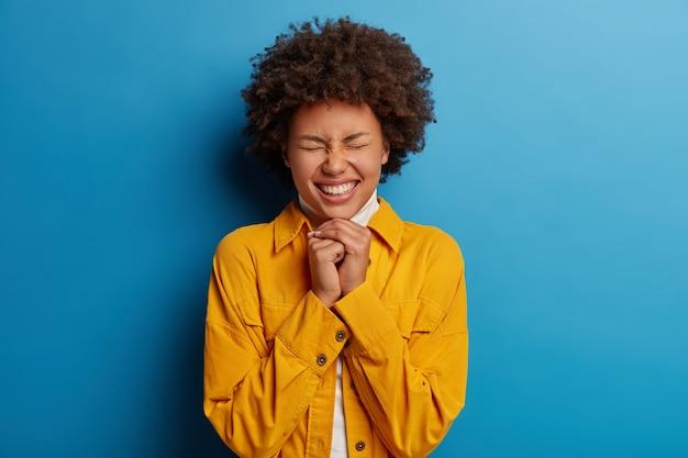 愛らしいエスニック女性は、歯を見せる笑顔、あごの下に手を保ち、目を閉じ、幸せを表現し、スタイリッシュな服を着て、丁寧な落ち着いた表情を持ち、青い背景の上に孤立しています