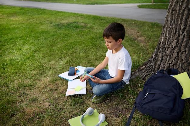 Очаровательный европейский ученик начальной школы учится в общественном парке, держит в руках мобильный телефон и делает уроки на открытом воздухе через интернет. ребенок-ученик решает математические задачи в парке после школы.