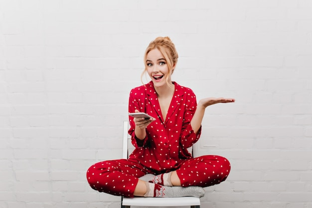 Adorable excited lady with blonde hair sitting on white wall. good-looking girl in red night-suit holding cell and expressing positive emotions.