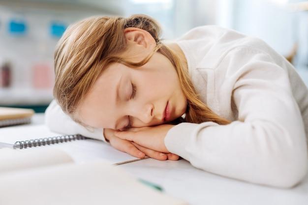 Очаровательная белокурая маленькая девочка спит над своими книгами, сидя за столом и делая домашнее задание