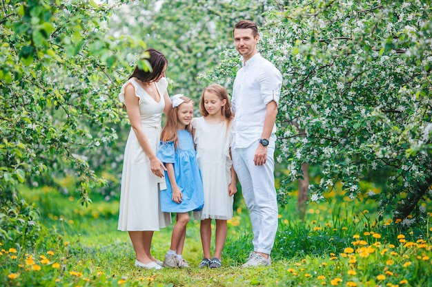 Adorable family in blooming cherry garden on beautiful spring day