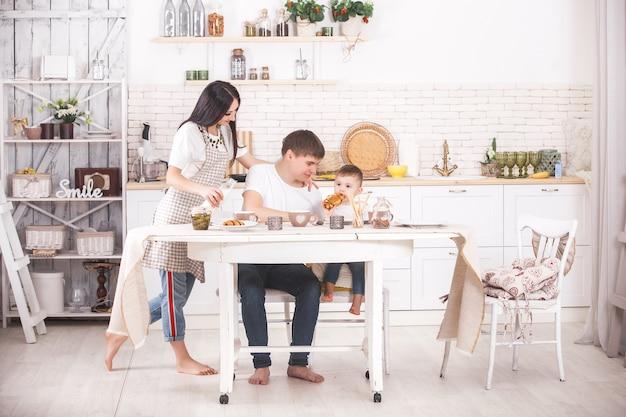 愛らしい家族一緒に料理します。朝食や夕食を持っている台所で若い家族。ママ、パパとその小さな子供が食事を準備しています。
