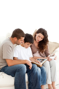 Adorable family looking at a photo album together on the sofa