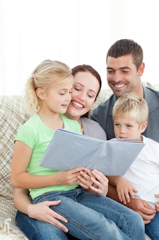 Adorable family reading a book together in the living-room