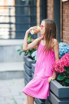 ヨーロッパの都市の屋外で愛らしいファッションの小さな女の子