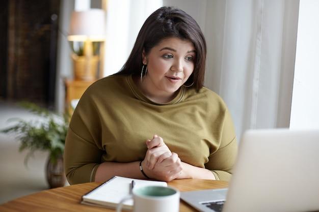 사랑스러운 유행의 젊은 더하기 크기의 여성이 열린 노트북 앞에 아늑한 카페테리아에 앉아 화상 통화를 통해 친구와 온라인 채팅을하는 동안 무료 wi-fi를 사용하여 흥분된 모습을 보였습니다. 필름 효과