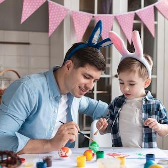 Очаровательный отец и сын красят яйца на пасху вместе
