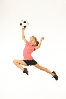 Прелестный футболист женского пола держит игровой мяч и кричит, прыгая в воздухе. изолированные на белом фоне