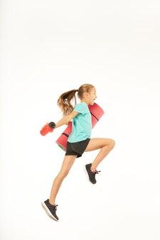 운동 매트와 상쾌한 스포츠 음료를 들고 공중에서 점프하는 사랑스러운 여자 아이. 흰색 배경에 고립