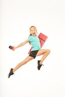 사랑스러운 여자 아이가 운동용 매트와 스포츠 음료를 들고 공중으로 뛰어오르고 소리를 지릅니다. 흰색 배경에 고립