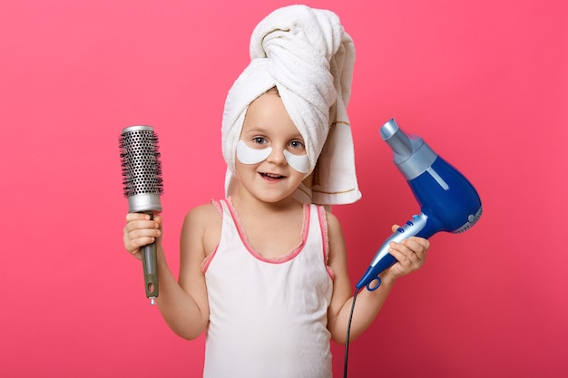Adorable female child holding hair dryer and comb in hands