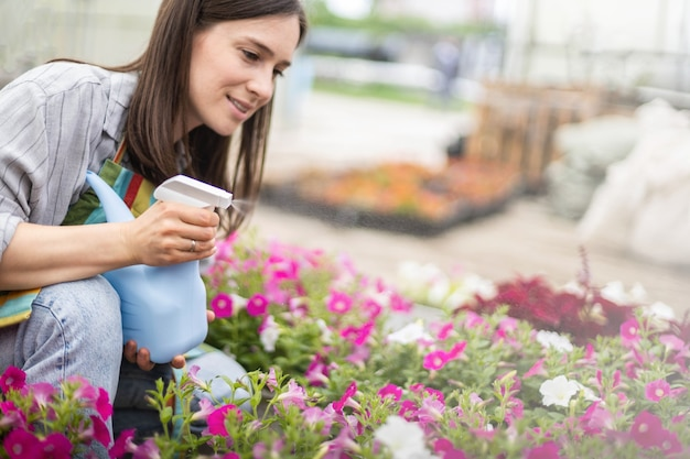 Adorable female florist spraying fresh water to petal leaves of flowers working at greenhouse
