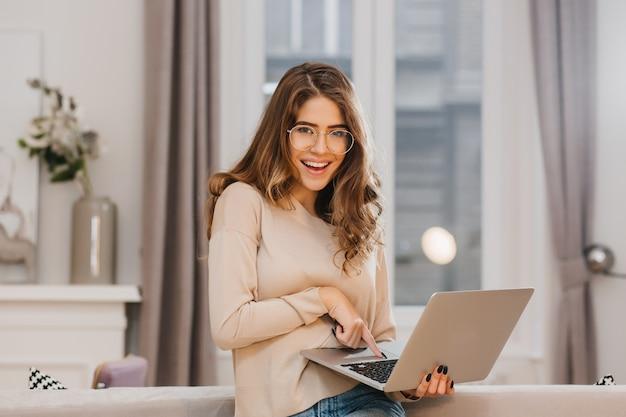 Очаровательная женщина-фрилансер в стильных очках с удовольствием позирует во время работы с ноутбуком