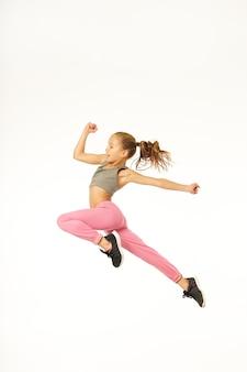 空中を走っているようにジャンプするスポーツウェアの愛らしい女性の子供。白い背景で隔離