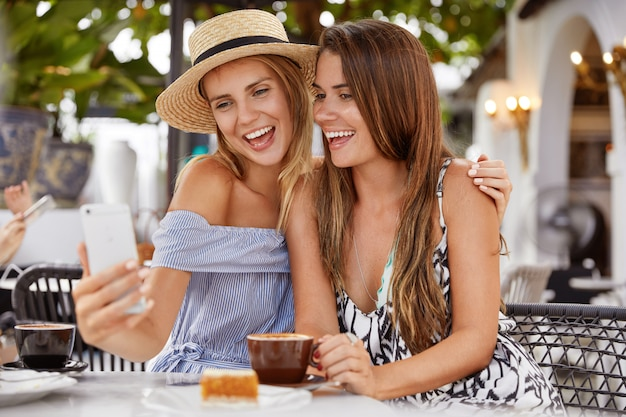 Adorable female lesbians cuddle and pose for selfie in modern cel phone, happy to spend time together at outdoor cafe, drink coffee, have positive smiles.