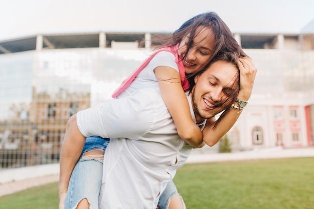 Очаровательная женская модель обнимает мужа, сидящего на спине