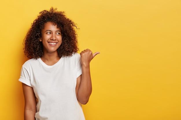 ふさふさした巻き毛の愛らしい女子学生は、親指を右に向け、幸せでリラックスした気分で、白いカジュアルなtシャツを着て、顔に誠実な笑顔を持ち、黄色の壁に隔離され、何か面白いものを示しています