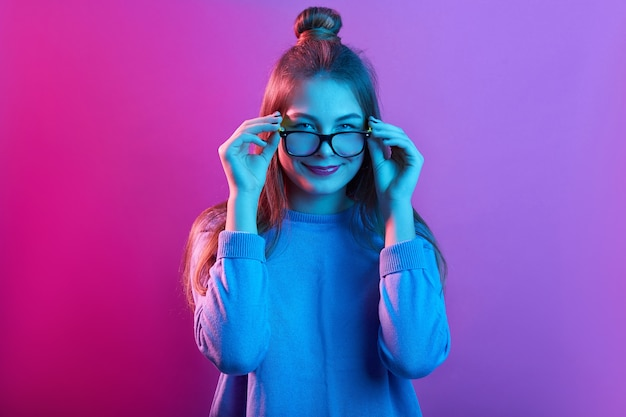 Adorable female touching frames of glasses, smiling delighted and looking at camera against pink neon wall