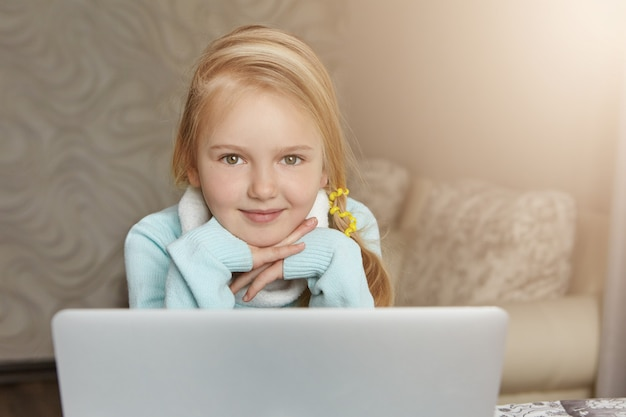 開いているラップトップの前に座っているポニーテールのブロンドの髪を持つ愛らしい一年生の女の子