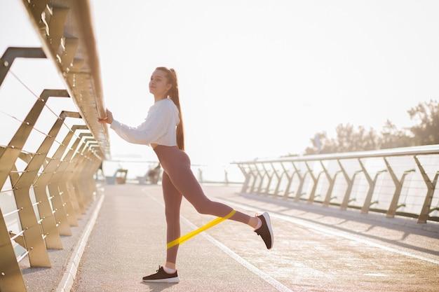 朝の橋で輪ゴムでエクササイズをしているスポーツアパレルに身を包んだ長い髪の愛らしいフィットの女性。テキスト用のスペース