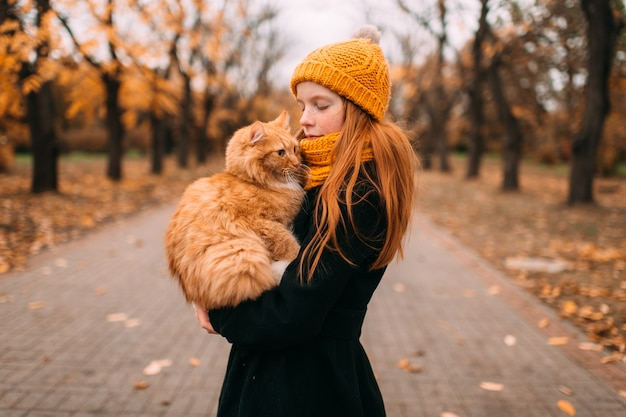 Adorable freckles girl with kind face expression holding her red cat in a valley of autumn park.