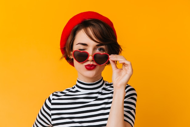 Adorable french lady posing in heart-shaped sunglasses