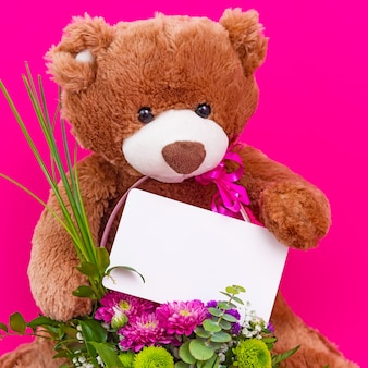 Adorable funny brown teddy bear holding white blank paper card