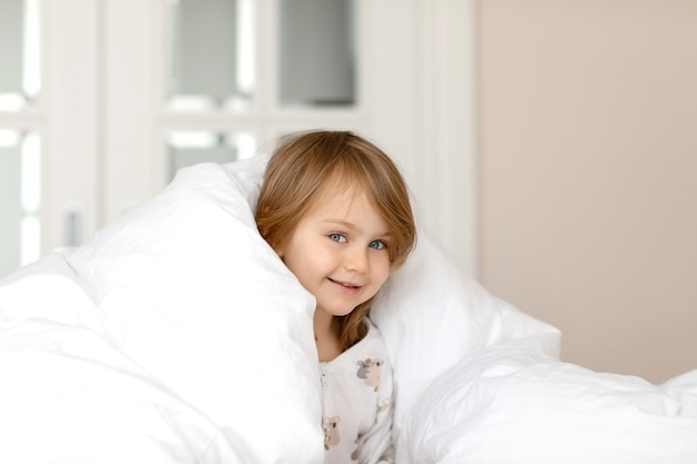 Adorable funny kid with blue eyes in pajamas lies in bed under a white fluffy blanket
