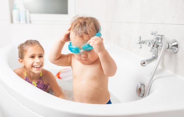 Очаровательный забавный маленький мальчик в синих плавательных очках стоит в ванной рядом со своей старшей сестрой