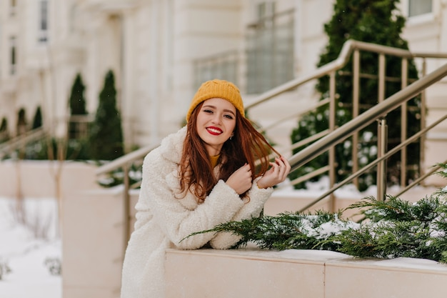 Adorable ginger girl in hat expressing positive emotions. gorgeous female model relaxing in winter.