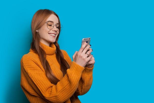 주근깨가있는 사랑스러운 생강 학생이 여유 공간이있는 파란색 벽에 노란색 스웨터를 입고 모바일로 채팅하고 있습니다.