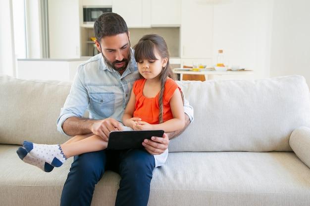 愛らしい少女と彼女のお父さんが一緒にタブレットで映画を見て。