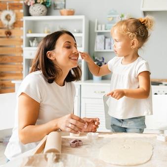 愛らしい少女と彼女の母親が小麦粉で遊んで