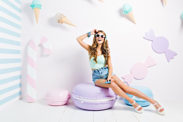Adorable girl in black glasses and white sandals chilling on macaroon chair and posing with hand up. indoor portrait of excited curly woman in denim shorts enjoying music and singing in candy room.