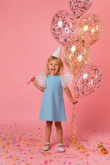 Adorable girl in costume with balloons and party hat