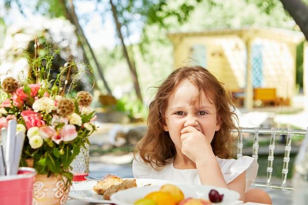 테라스에 있는 테이블에서 식사를 하는 사랑스러운 소녀