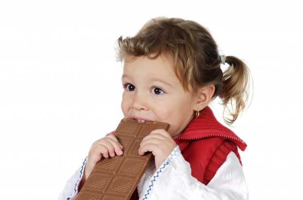 Adorable girl eating chocolate a over white background