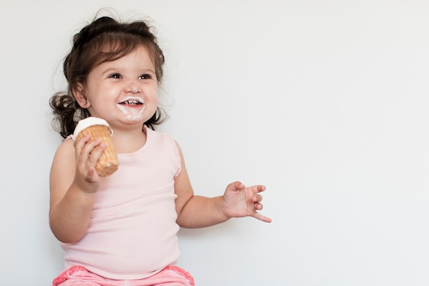 Adorable girl eating ice cream and looking away