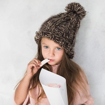 Adorable girl eating and wearing winter hat